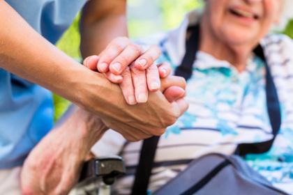 Altenpflegerin hält Hand von älterem Menschen