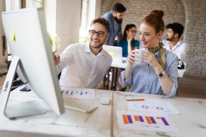 Digital-Marketing-Experten am Schreibtisch vor dem Monitor bei der Arbeit